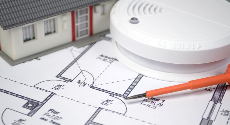 Rauchmelder mit Bauplan und Haus